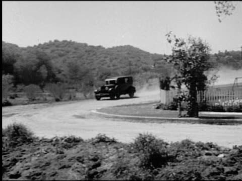 vídeos y material grabado en eventos de stock de b/w 1920s pan car speeding toward curve on road, crashing through guard-rail + flipping over - b roll