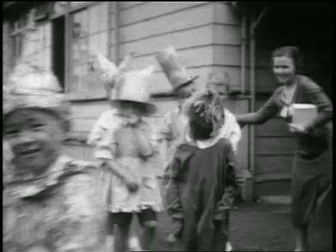 b/w 1920s children passing camera wearing halloween costumes outdoors / japan / home movie - halloween stock videos & royalty-free footage