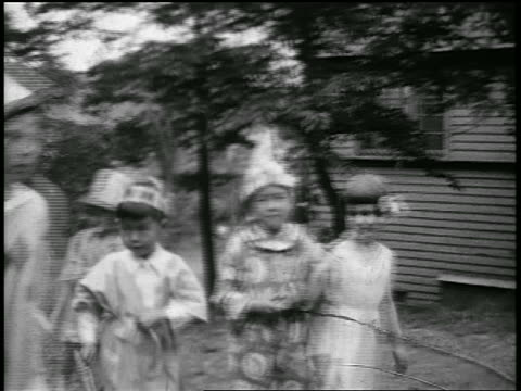 b/w 1920s children passing camera wearing halloween costumes outdoors / japan / home movie - 1920年点の映像素材/bロール