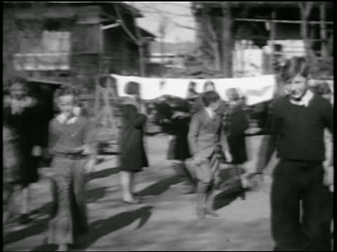 b/w 1920s children running + playing in schoolyard outdoors / japan / home movie - 1920年点の映像素材/bロール