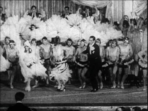B/W 1920s chorus line + man in tuxedo dancing in fancy floorshow / Paris, France / documentary