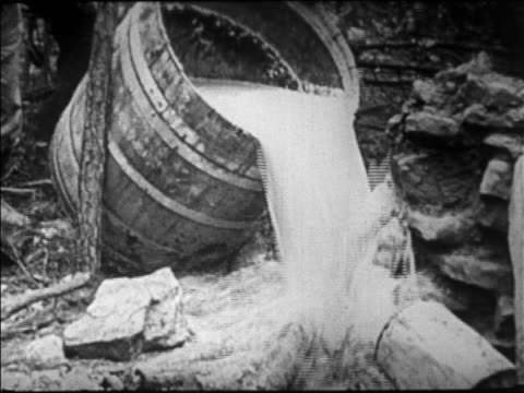 b/w 1920s close up barrel of moonshine being tipped out onto ground in florida swamp / prohibition - 禁酒法点の映像素材/bロール