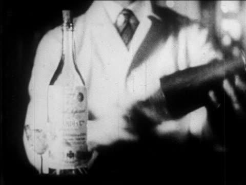 B/W 1920s close up bartender using shaker / bottle of liquor in foreground / newsreel