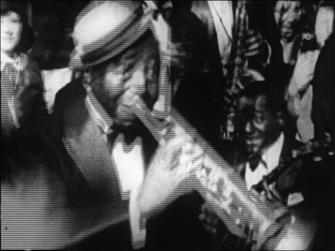B/W 1920s close up Black man playing trumpet in band in nightclub / Paris, France / documentary