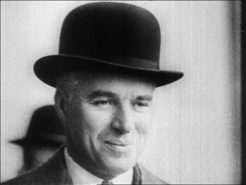 B/W 1920s close up Charles Chaplin in hat smiling / Paris / documentary