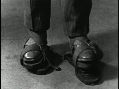 B/W 1920s close up feet of man wearing shoes with springs under them + bouncing / short