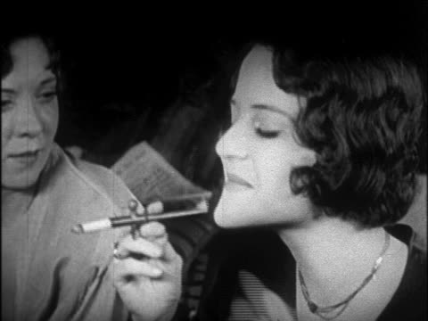 b/w 1920s close up flappers smoking cigarettes thru cigarette holders  / newsreel - sigaretta video stock e b–roll