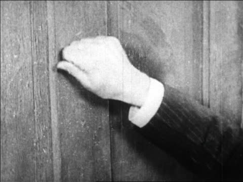 B/W 1920s close up hand of man knocking on door / newsreel