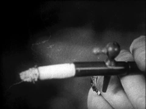 b/w 1920s close up hand of woman smoking cigarette thru cigarette holder  / newsreel - smoking activity stock videos and b-roll footage