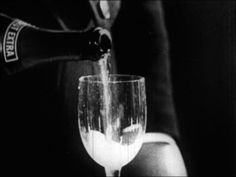 vídeos de stock, filmes e b-roll de b/w 1920s close up hand pouring glass of champagne / paris, france / documentary - 1920