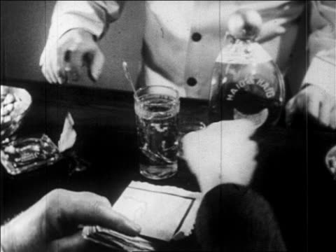 B/W 1920s close up hand throwing money onto bar + grabbing bottle of liquor in speakeasy / newsreel
