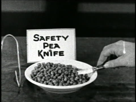 """B/W 1920s close up hand with knife invention scooping peas from plate by """"Safety Pea Knife"""" sign / short"""