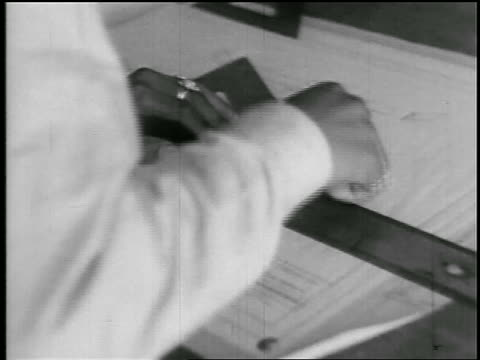b/w 1920s close up hands of man using drawing tools at drafting tables in school / educational - architect点の映像素材/bロール