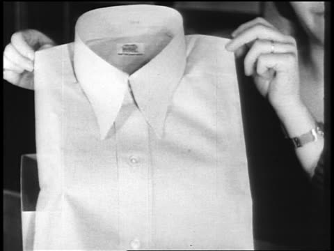 b/w 1920s close up hands of woman holding man's dress shirt / newsreel - department store stock videos and b-roll footage