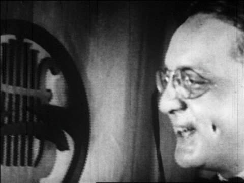 vídeos de stock, filmes e b-roll de b/w 1920s close up man in pince nez talking into microphone in radio studio - comentarista
