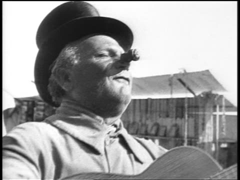 b/w 1920s close up man playing guitar + singing outdoors / cork on nose / paris / documentary - nur männer über 40 stock-videos und b-roll-filmmaterial