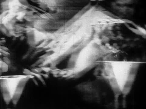b/w 1920s close up men pouring cans of bootleg liquor into bottles / prohibition / newsreel - 禁酒法点の映像素材/bロール
