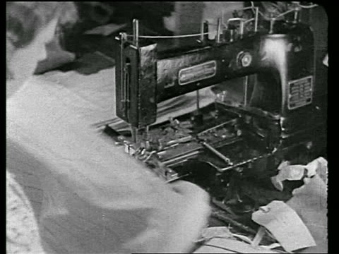 b/w 1920s close up over-the-shoulder woman sewing buttons on cloth on sewing machine in clothing factory / newsreel - textilindustrie stock-videos und b-roll-filmmaterial