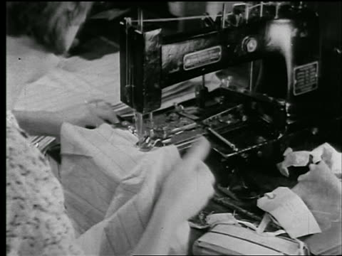 b/w 1920s close up over-the-shoulder woman sewing buttons on cloth on sewing machine in clothing factory / news. - sewing machine stock videos & royalty-free footage