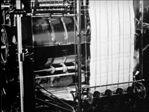 B/W 1920s close up printing press running in newspaper printing plant / newsreel