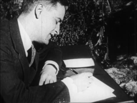 b/w 1920s close up profile f scott fitzgerald writing at desk outdoors / france / newsreel - f. scott fitzgerald writer stock videos and b-roll footage