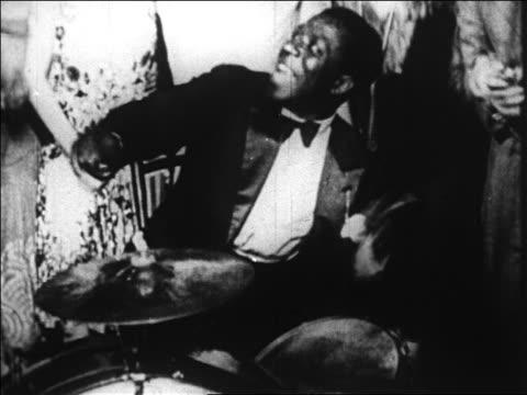 B/W 1920s close up smiling Black man playing drums in band in nightclub / Paris, France / documentary