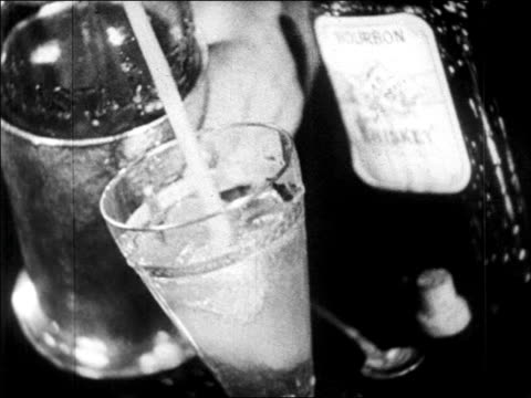 b/w 1920s close up soda water squirting into glass of liquor / newsreel - prohibition stock videos & royalty-free footage