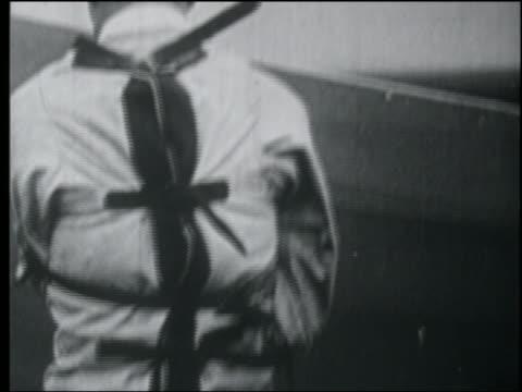 B/W 1920s close up stuntman Joe Campi in straitjacket talking to camera