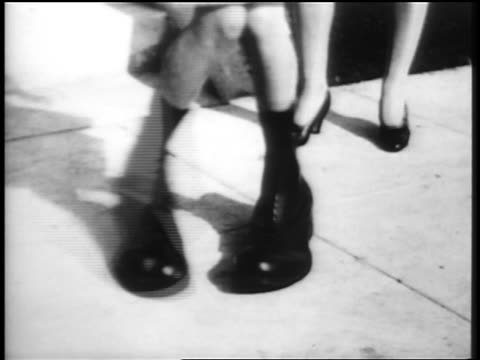 B/W 1920s close up tilt up girl in huge oversized shoes dancing Charleston / mother clappin in background / educational