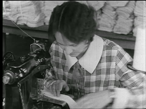 b/w 1920s close up woman sewing collar on sewing machine in clothing factory / newsreel - textile mill stock videos & royalty-free footage