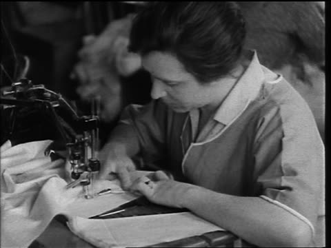 b/w 1920s close up woman working quickly at sewing machine in factory - sewing machine stock videos & royalty-free footage