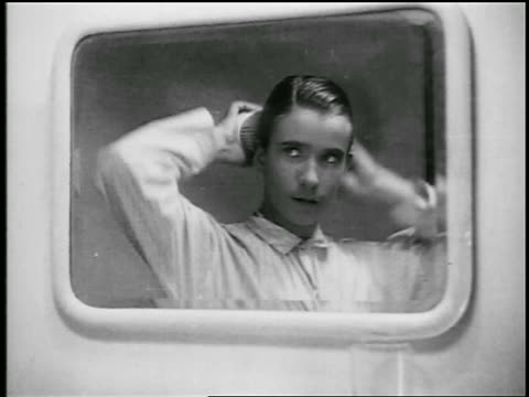 stockvideo's en b-roll-footage met b/w 1920s close up young man brushing hair in mirror with two brushes / educational - haar borstelen