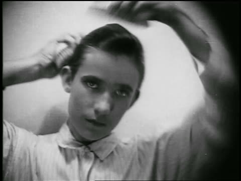 B/W 1920s close up young man brushing hair with two brushes / educational