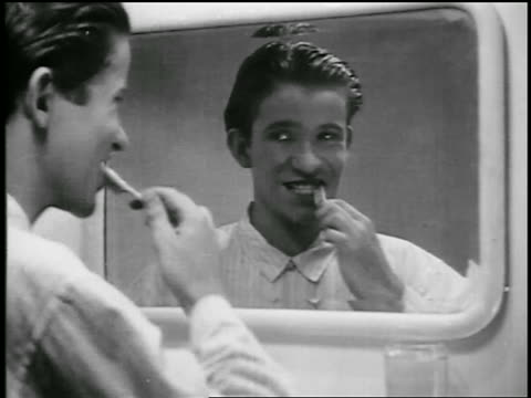 b/w 1920s close up young man brushing teeth in bathroom mirror  / educational - 歯点の映像素材/bロール