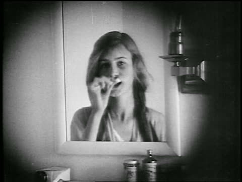 B/W 1920s close up young woman brushing teeth in bathroom mirror  / educational