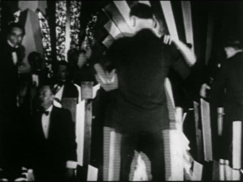 B/W 1920s couple dancing on stilts in NYC nightclub / band in background / newsreel