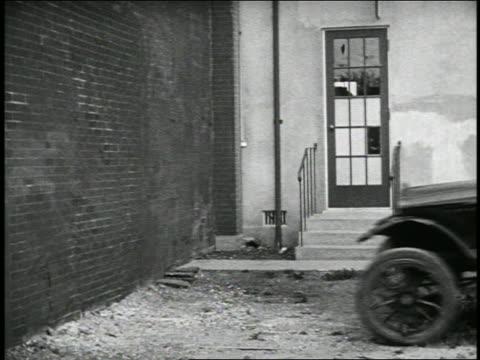 b/w 1920s couple in car crashing thru building + disrupting card game (3 shots) / feature - vårdslös bildbanksvideor och videomaterial från bakom kulisserna