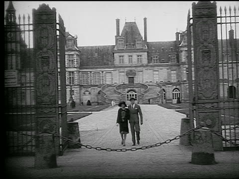 B/W 1920s couple walking away from Chateau de Fontainebleau through gate + getting in car / France