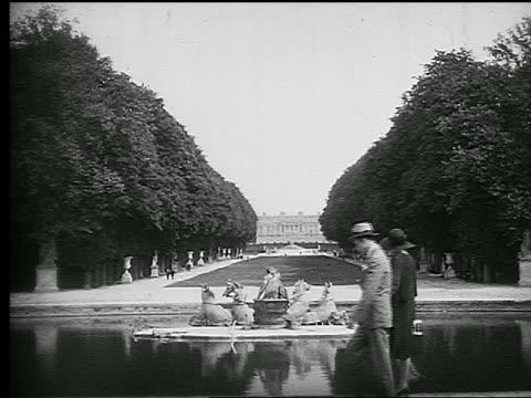 vídeos de stock, filmes e b-roll de b/w 1920s couple walking next to apollo fountain looking toward palace on grounds of versailles - jardim de versailles