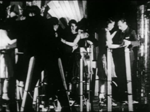 b/w 1920s pan couples dancing on stilts in nyc nightclub / man falls over / newsreel - stilts stock videos and b-roll footage
