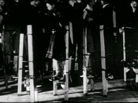 b/w 1920s couples dancing on stilts in nyc nightclub / one woman falls / newsreel - stilts stock videos and b-roll footage