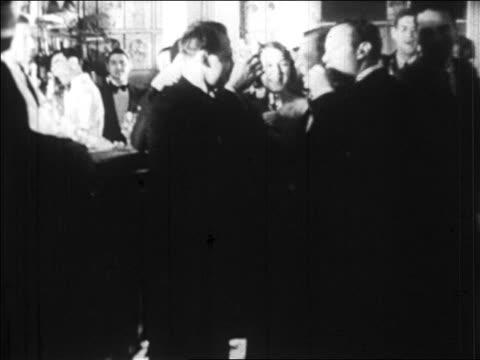 stockvideo's en b-roll-footage met b/w 1920s couples in formalwear drinking at bar / paris, france / newsreel - formele kleding