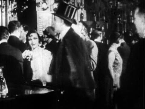 B/W 1920s couples in formalwear drinking at party / Paris, France / newsreel