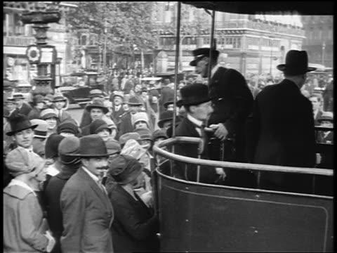 vidéos et rushes de b/w 1920s crowd boarding trolley on city street / 3 shots / paris / documentary - 1920