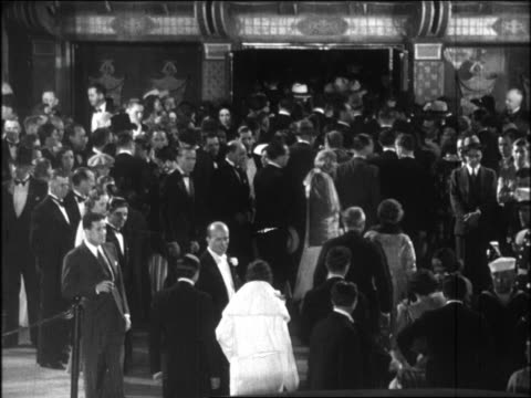 vídeos de stock, filmes e b-roll de b/w 1920s crowd in formalwear entering graumann's chinese theatre for movie premiere at night - estreia