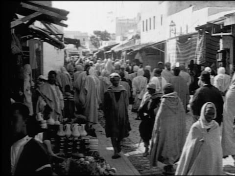 B/W 1920s crowd of people + vendors in native dress in outdoor market (souk) / Kairwan, Tunisia