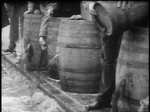 b/w 1920s crowd tasting liquor spilling from wooden barrel / prohibition / feature film - 禁酒法点の映像素材/bロール