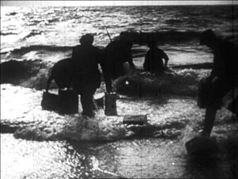 B/W 1920s DISSOLVE men carrying boxes of bootleg liquor from ocean to shore / Prohibition / newsreel