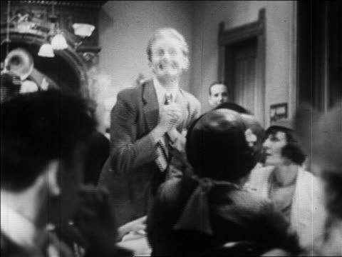 stockvideo's en b-roll-footage met b/w 1920s drunk man in speakeasy being forced to sit down / prohibition / newsreel - middelenmisbruik