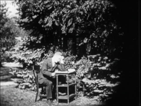 b/w 1920s f scott fitzgerald writing at desk outdoors / france / newsreel - f. scott fitzgerald writer stock videos and b-roll footage